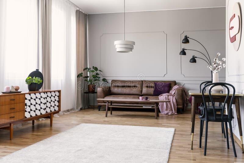 Armario de madera en interior brillante de la sala de estar con el sofá de cuero y sillas en la tabla Foto verdadera imagen de archivo libre de regalías