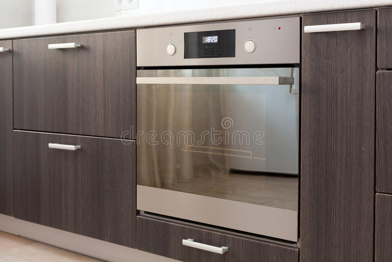 Armarios de cocina con las manijas del metal y el horno eléctrico incorporado imagen de archivo