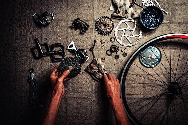 Armarna för man` s reparerar cykeln överallt finns det reservdelar utan några logoer royaltyfria bilder