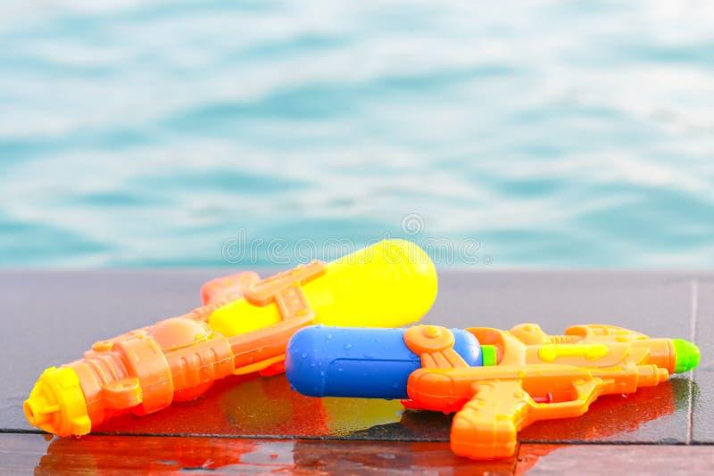 Armas de água coloridas pela piscina imagens de stock royalty free