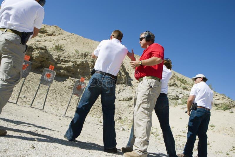 Armas de Assisting People Aiming del instructor en la gama de leña fotos de archivo libres de regalías