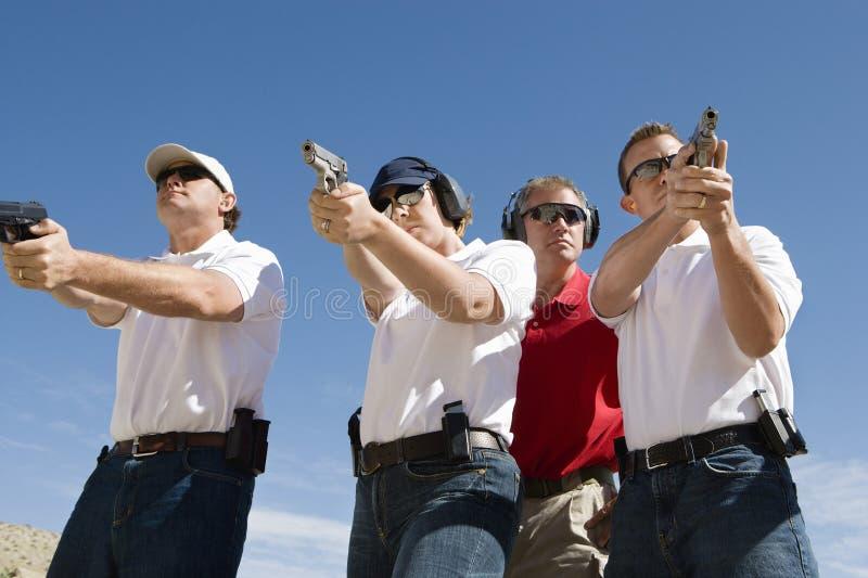 Armas de Assisting People With del instructor en la gama de leña imagenes de archivo