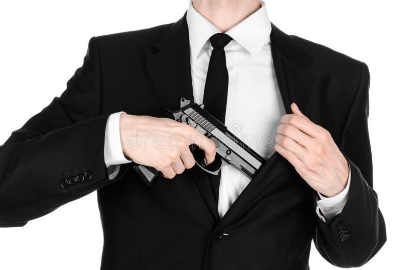 Armas de fuego y tema de la seguridad: un hombre en un traje negro que sostiene un arma en un fondo blanco en estudio imagenes de archivo