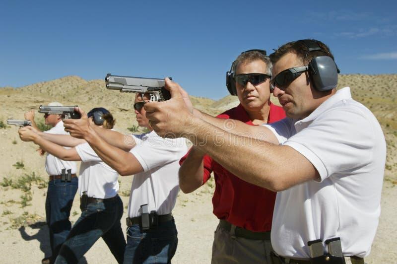 Armas de la mano de Assisting Officers With del instructor en la gama de leña foto de archivo libre de regalías