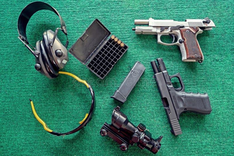 Armas de la visión superior: Dos pistolas, manguitos del oído y balas y arma semiautomático para la autodefensa en la tabla verde imagen de archivo libre de regalías