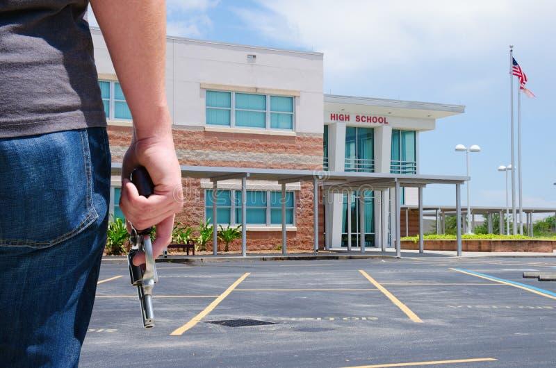 Armas en hombre joven de la escuela con el arma en la escuela foto de archivo