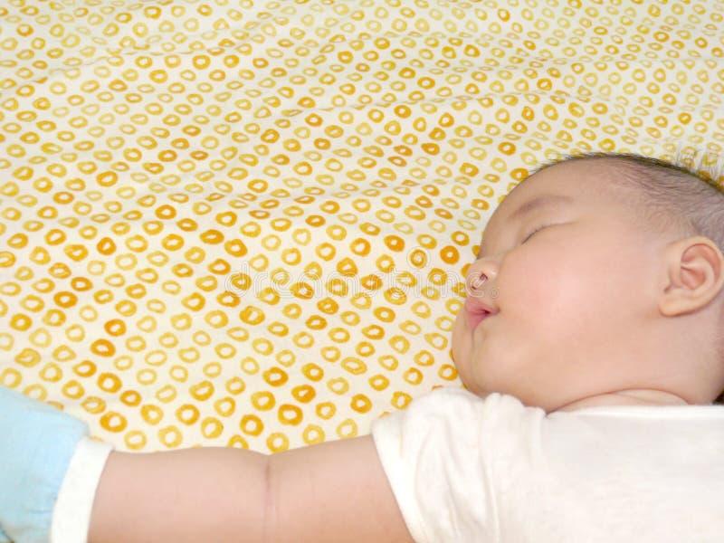armasiatet behandla som ett barn sträckt att sova för sida arkivfoton