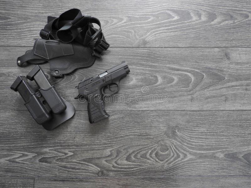 Armatni czerń, dodatkowi magazyny i rzemienny holster na popielatym tle, zdjęcia stock