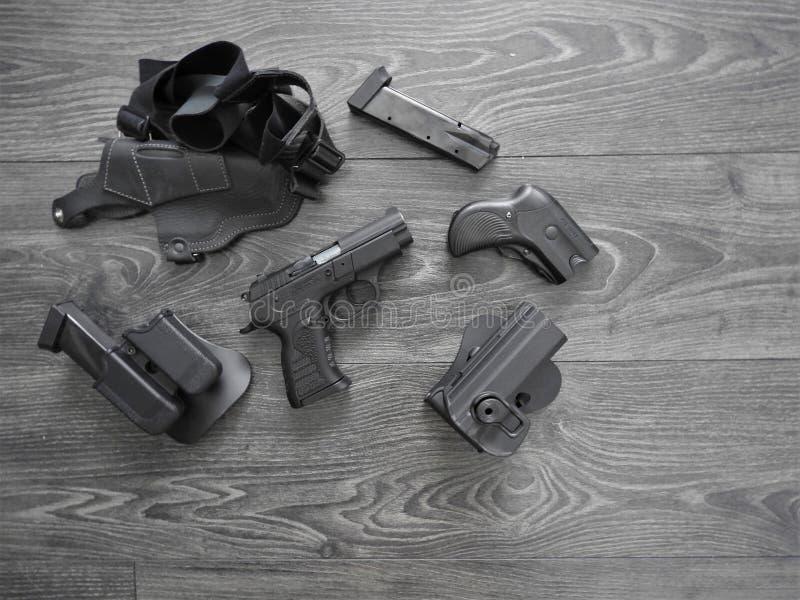 Armatni czerń, dodatkowi magazyny i rzemienny holster na popielatym tle, obraz stock