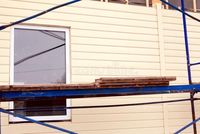 Armatura intorno alla casa vicino alla parete con la finestra ed il raccordo beige fotografia stock