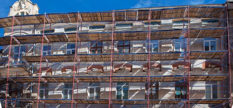 Armatura vicino ad una casa in costruzione per gli impianti esterni del gesso, l'alta costruzione di appartamento nella città, la immagine stock