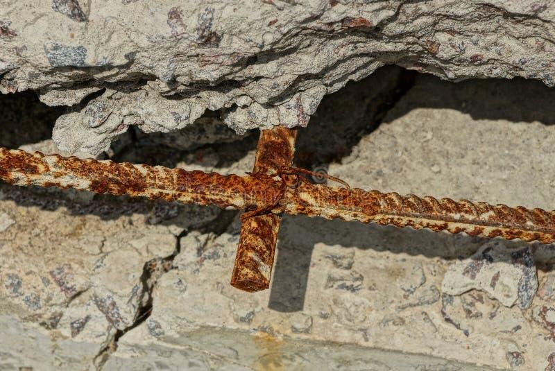 Armature утюга Брауна ржавый в серой старой бетонной стене стоковая фотография