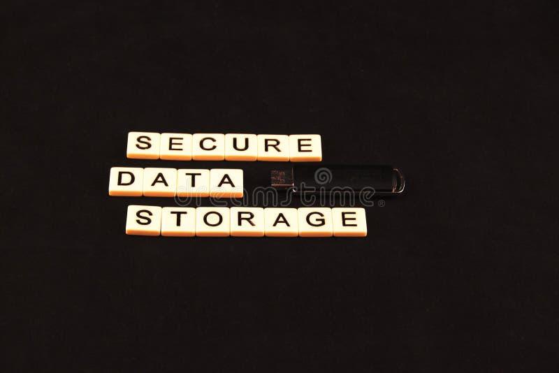 Armazenamento de dados seguro soletrado para fora com telhas em um fundo preto com uma movimentação de USB à direita imagens de stock