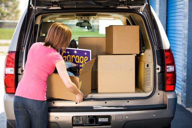 Armazenamento: Sobras ausentes de embalagem da venda de garagem da mulher imagens de stock