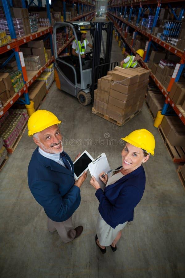 Armazene o gerente e o cliente que guardam a tabuleta e a prancheta digitais fotos de stock