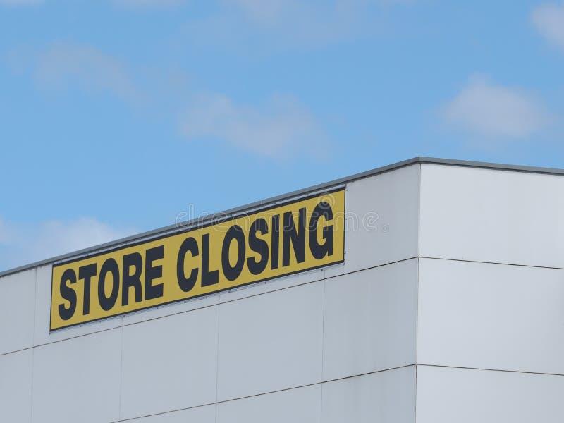 Armazene o preto de fechamento em letras amarelas em uma construção industrial claded branco fotos de stock