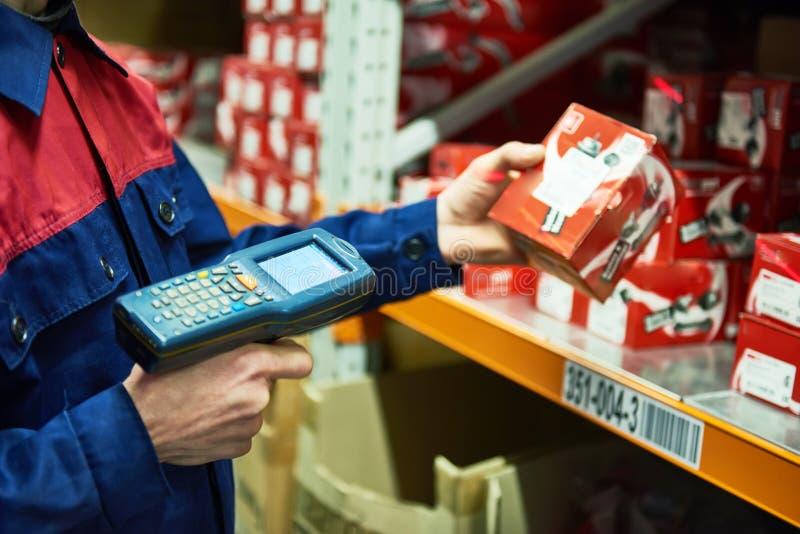 Armazene a peça sobresselente do automóvel da exploração do trabalhador com o varredor do código de barras do laser foto de stock