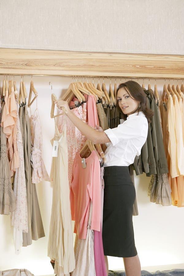 Armazene a roupa de trabalho e de suspensão do assistente na loja fotografia de stock royalty free
