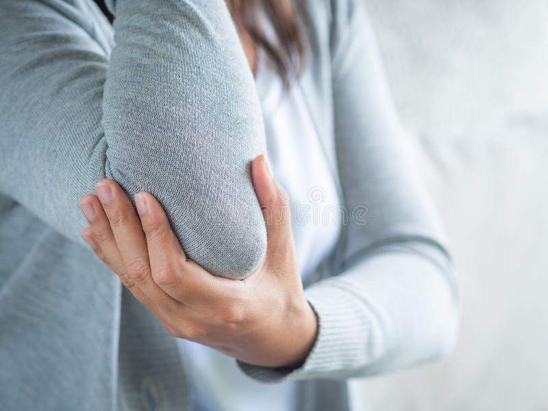 Armbåge för ` s för Closeup kvinnlig Armen smärtar och skadan Hälsovård och med royaltyfri fotografi