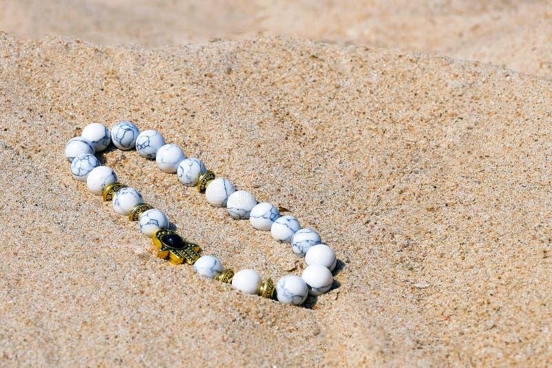 Armband av lasursten på sanden Vita runda pärlor på tråden Närbild för bästa sikt royaltyfria foton