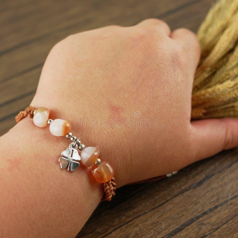 Armband för kvinnahandledkläder på träbakgrund arkivfoton