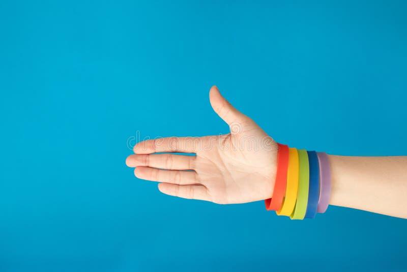 Armband för armband för regnbågeflagga LGBT på den kvinnliga handen på blå bakgrund arkivbild