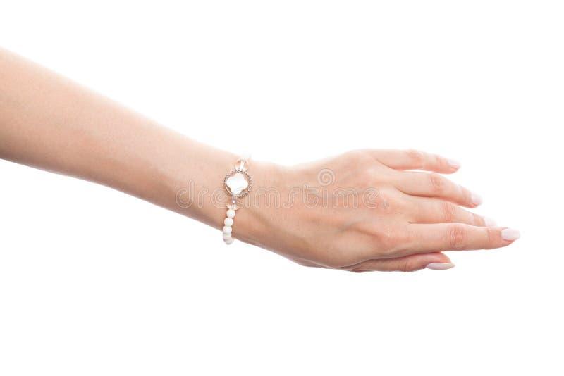 Armband för smycken för härlig kvinnahand bärande med pärlemo och pärlor som isoleras på vit bakgrund royaltyfria foton