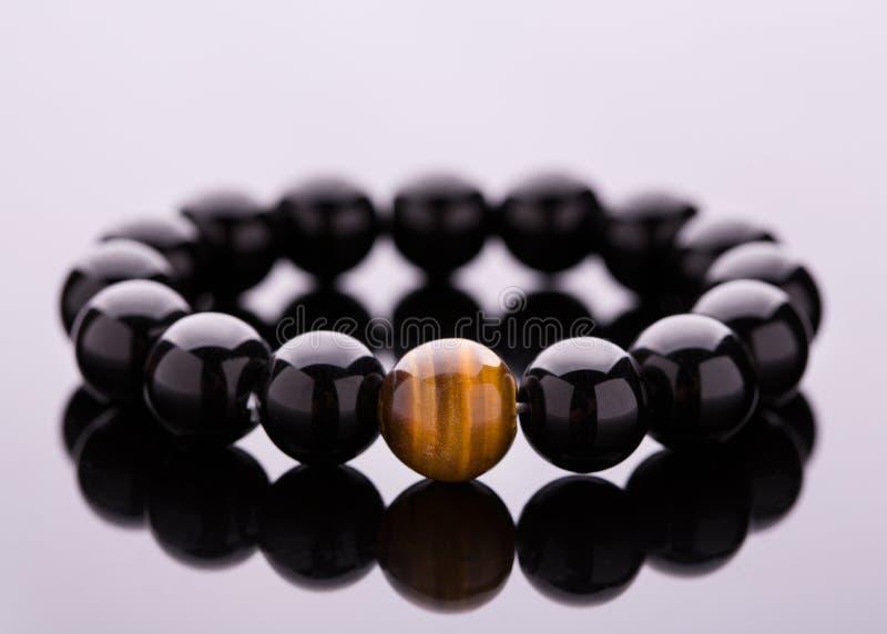 Armband från svarta runda stenar som ligger på en spegelyttersida arkivfoton