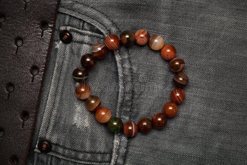 Armband på armen på bakgrunden av jeans, bästa sikt arkivfoto