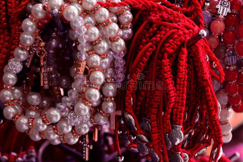 Armband van rode draad en parels wordt gevlecht die amulet tegen het kwade oog op pols van Jeruzalem, Israël stock foto