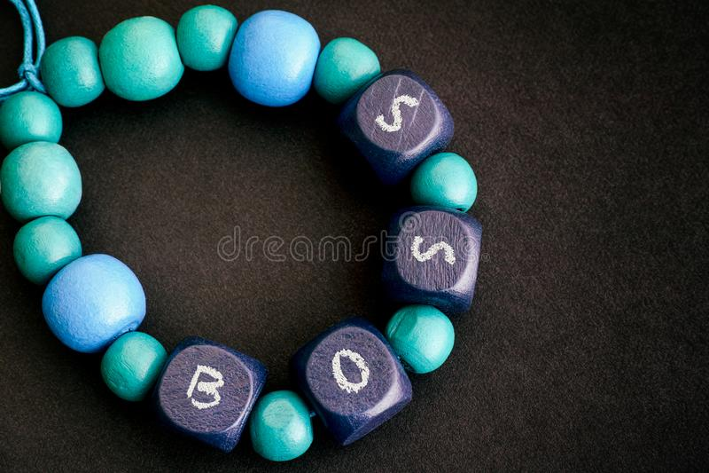 Armband von blauen Holzperlen mit Buchstaben beherrschen auf schwarzem Hintergrund stockfotografie
