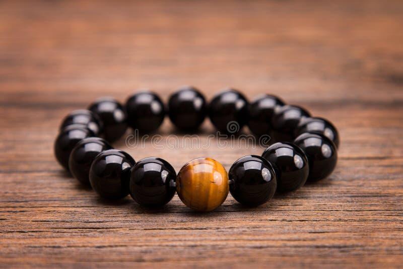 Armband von den runden schwarzen Steinen, die auf einem hölzernen Hintergrund liegen stockfotos