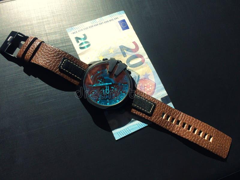 Armbandsuret med piskar remmen nära sedeln på en mörk bakgrund fotografering för bildbyråer