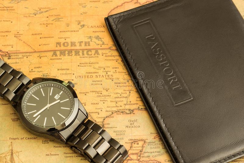 Armbanduhr und Pass auf dem Tisch mit einer Karte von Nordamerika lizenzfreies stockbild