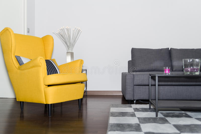 Armchair and Graceful Modern Gray Sofa Couch. Classical Style Yellow Armchair and Graceful Modern Gray Sofa Couch in Vintage Room with Fashion Lamp and Carpet in stock images