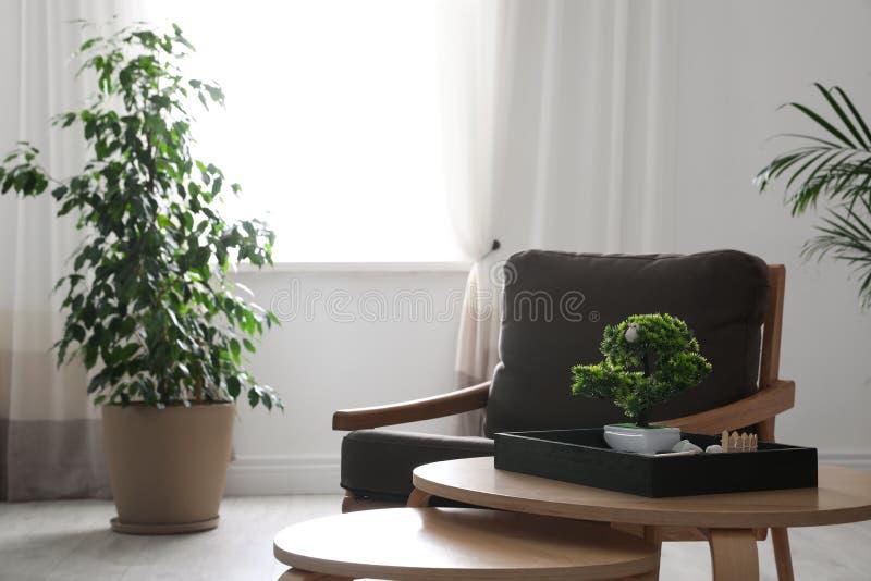 Armchair, miniature zen garden and green plants in room. Home design ideas royalty free stock image