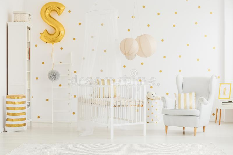 Armchair next to crib. Grey armchair with striped cushion standing next to white crib with canopy in baby room stock photography