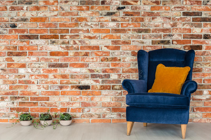 Armchair with orange pillows. Blue armchair with orange pillow and small decorative plants royalty free stock photo