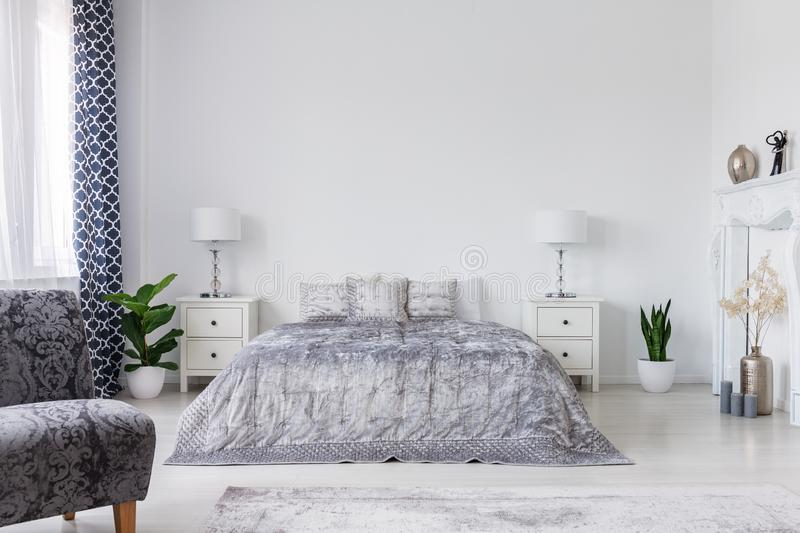 Armchair and plants in white elegant bedroom interior with bed between cabinets with lamps. Real photo. Concept stock images