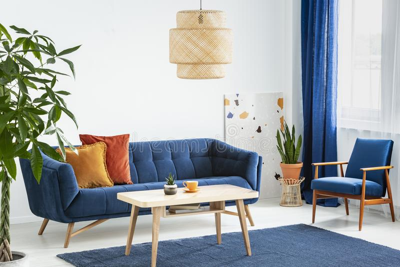Armchair and sofa in blue and orange living room interior with lamp above wooden table. Real photo. Concept royalty free stock images