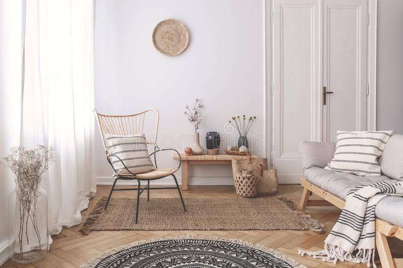 Armchair and sofa with patterned pillows in white flat interior with plants and round rug. Real photo. Concept stock image
