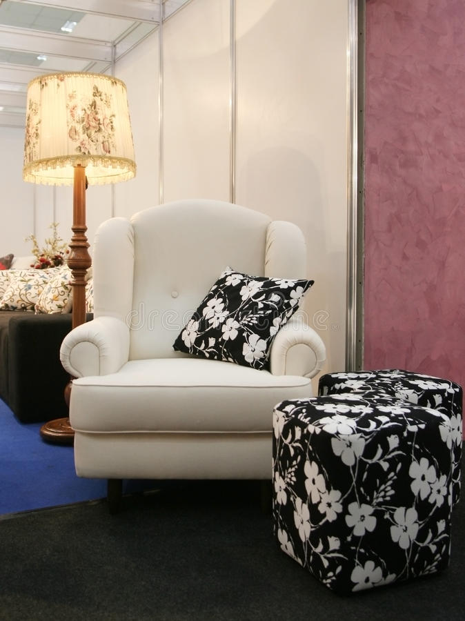 Armchair. White armchair with fabric stools and pillow, lamp in background royalty free stock photography