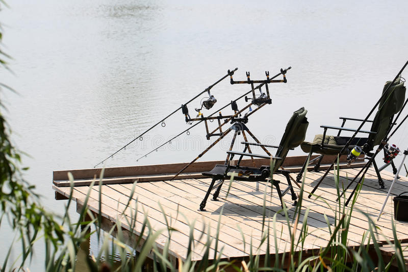 Armchairs with fishing tackle on pier stock photography