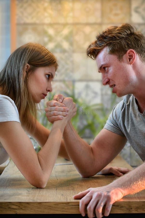 Armdrückenherausforderung zwischen jungem Mann und Frau, Paarhaushaltskonflikt und Kampf lizenzfreies stockbild