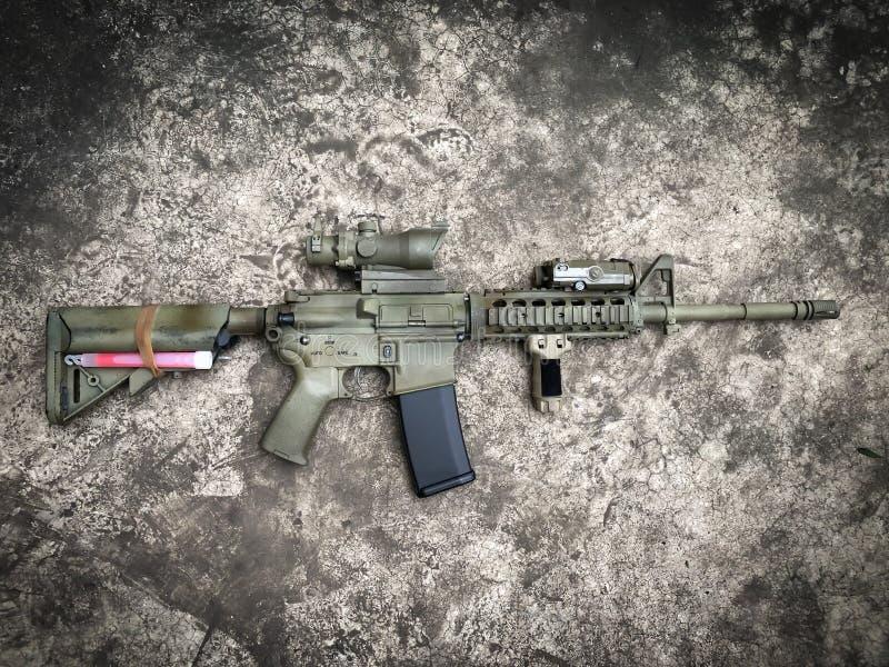 Arme à feu d'airsoft de fusils d'assaut de dessert au sol photographie stock