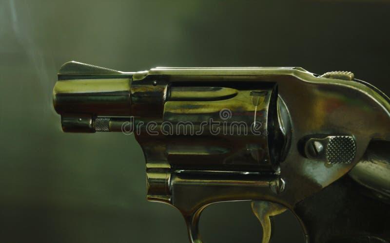 Arme à feu de revolver avec de la fumée flottant dans le ciel après pousse sur le fond noir images stock