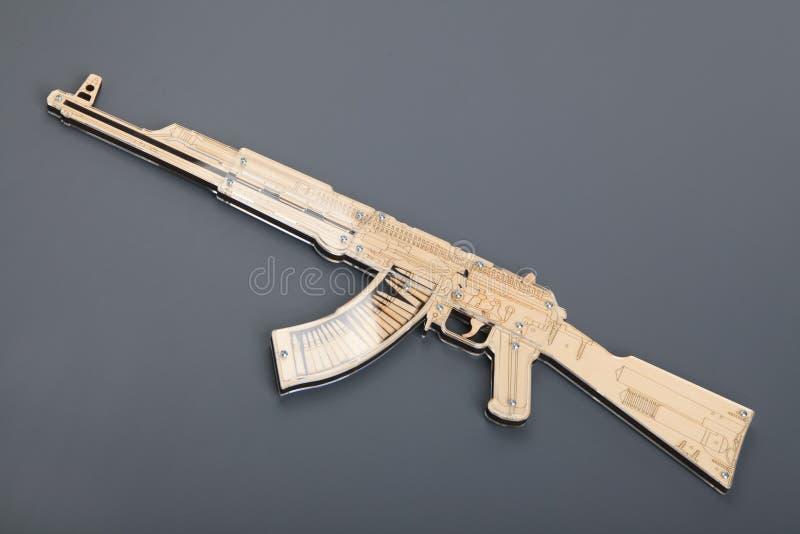 Arme à feu en bois de jouet sur le fond gris photographie stock libre de droits