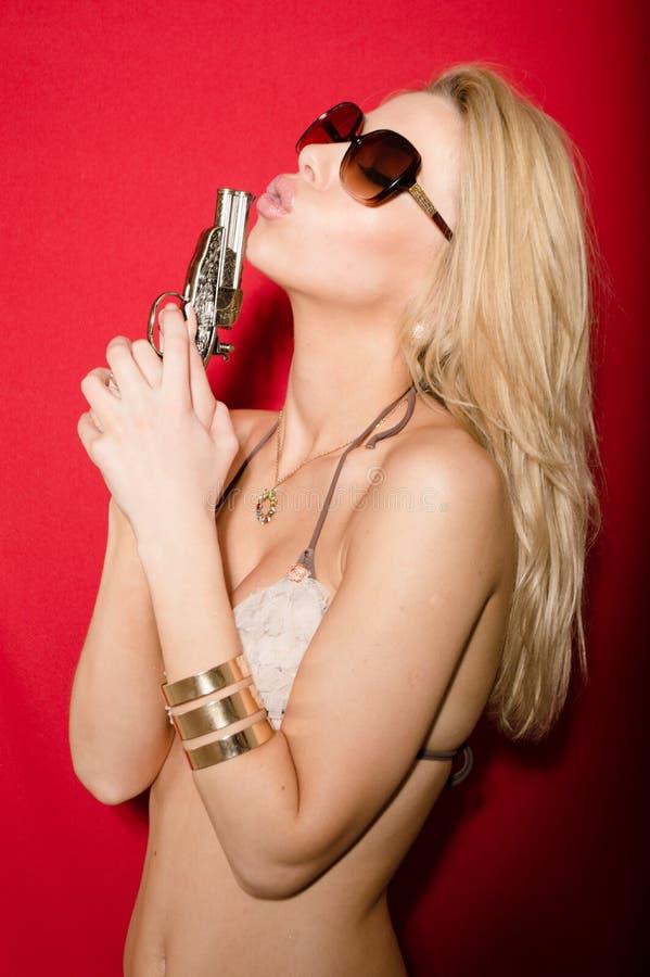 Arme à feu et bikini : belle jeune femme blonde sexy dans le bikini tenant l'arme à feu sur le fond rouge photo libre de droits