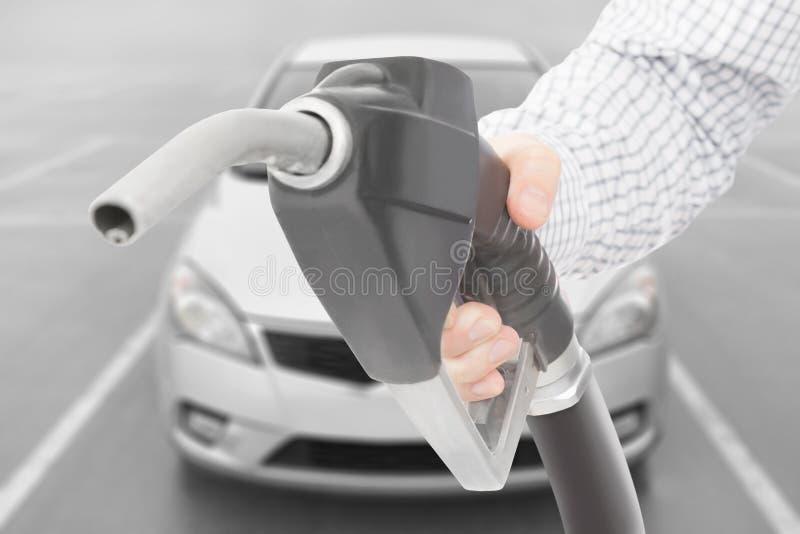 Arme à feu noire de pompe à essence de couleur à disposition avec la voiture sur le fond photographie stock libre de droits