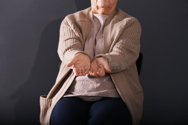 Arme ältere Frau, die um Geld auf dunklem Hintergrund bittet stockfotos
